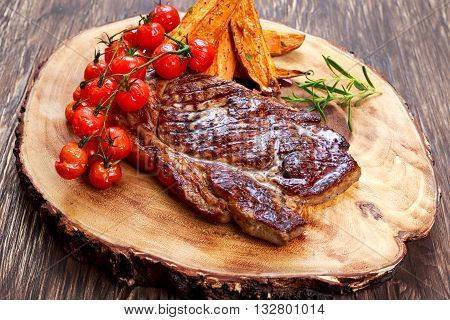 Grilled Beef Sirloin Steak on wooden board with vegetables