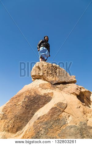 ASWAN, EGYPT - FEBRUARY 7, 2016: Local tourist standing on big rock in desert, Egypt.