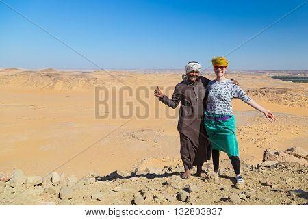 ASWAN, EGYPT - FEBRUARY 7, 2016: Nubian man wearing traditional clothing posing with european tourist.