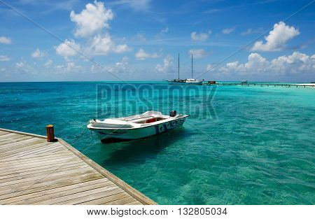 White boat moored to the wooden jetty in blue Maldivian lagoon.