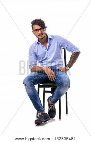 Portrait of brunette young man in light blue shirt and jeans, sitting on chair in studio shot isolated against white background. Full length photo