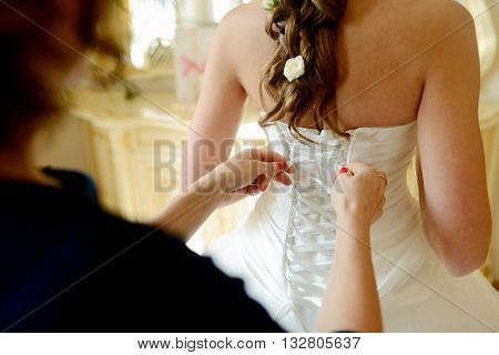 Bridesmaid Is Lacing White Wedding Dress For Beautiful Bride. Beauty Model Girl In Bridal Gown For M