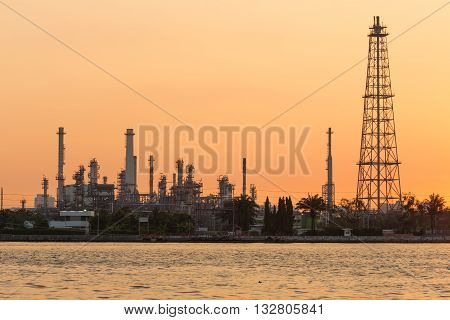 Sunrise riverfront over Oil refinery, heavy industry background