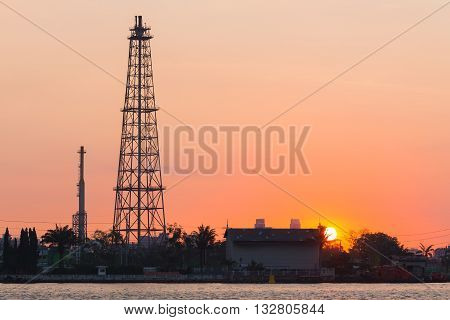 Oil refinery tower during sunrise, heavy industry background