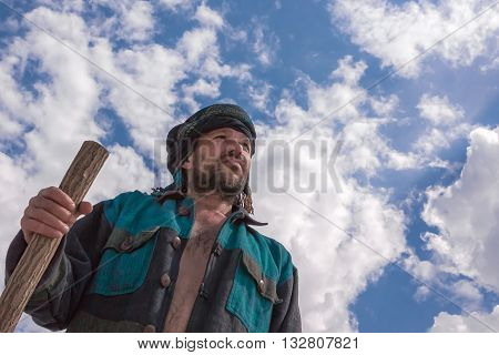 Man in his turban leaning on the stick looks into the distance under a blue sky with beautiful clouds bottom view.