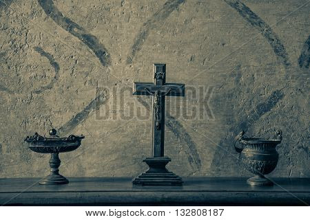 An ancient and weathered crucifix on a wood table between bronze vases