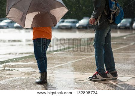 Two boys stand in the rain one of them is holding an umbrella