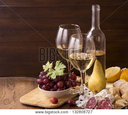 Wine and grapes in vintage setting on wooden table