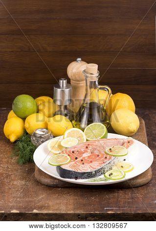Steak of red fish and sliced lemons on white