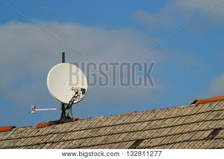 Satellite dish on a roof with defective roof ridge .