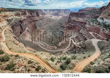 A 4WD vehicle makes its way down a dirt road through the Shafer Switchbacks, in the Islands in the Sky District of Canyonlands National Park, near, Moab Utah.