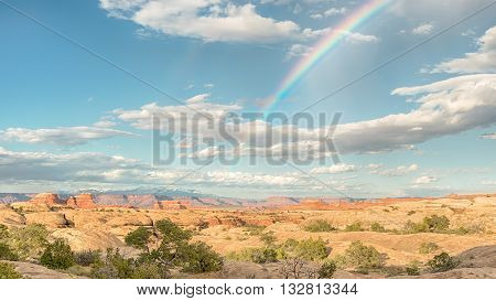 A rainbow arcs across the sky towards the La Sal mountains, in the Needles District of Canyonlands National Park, near Moab, Utah.