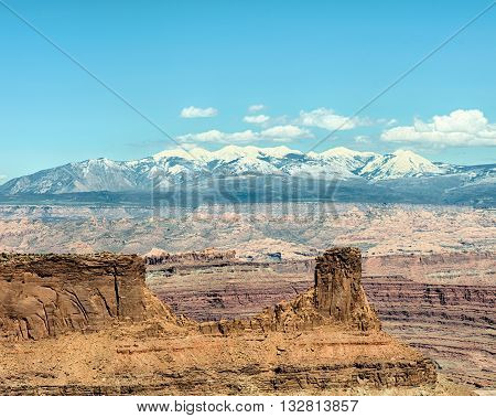 Snow-capped La Sal mountains rise above a butte on the East Rim Trail, in Dead Horse State Park, near Moab, Utah.