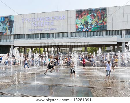 Moscow - May 9 2016: Wet happy people running between jets of water in a large musical fountain Muzeon park and the orchestra plays the music and a lot of people rest May 9 2016 Moscow Russia