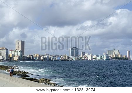 HAVANA - NOVEMBER 29: Two boys enjoy the sunny weather and walking on the breakwater in Havana's Malecon promenade on 29 November 2015 in Havana, Cuba. Malecon promenade it is famous place in Havana