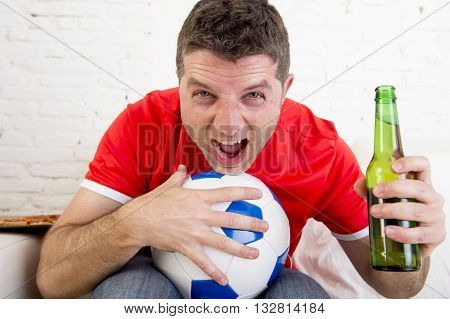 young fan man watching football game on television wearing team jersey celebrating goal happy on sofa couch at home holding soccer ball and beer bottle in crazy enthusiastic face expression