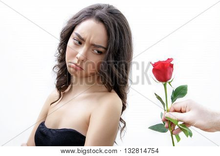 Beautiful upset girl receives one red rose. She is looking over her shoulder and pouts. Men's hand holding one rose. Girl is white with bushy brown hair. Isolated on white background.