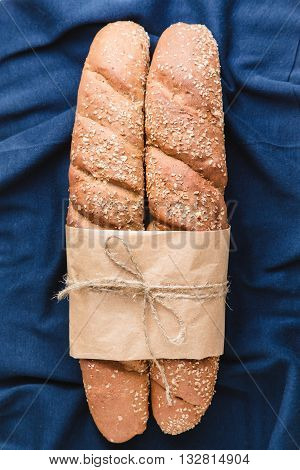 Two loafs of French baguette bread tied with paper and string on blue textile background