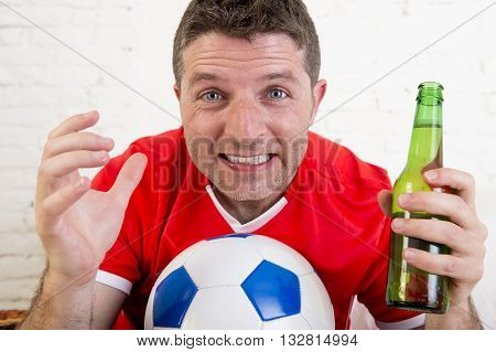close up face of young fan man watching football game on television wearing team jersey suffering nervous and stress on sofa couch at home holding soccer ball and with beer bottle