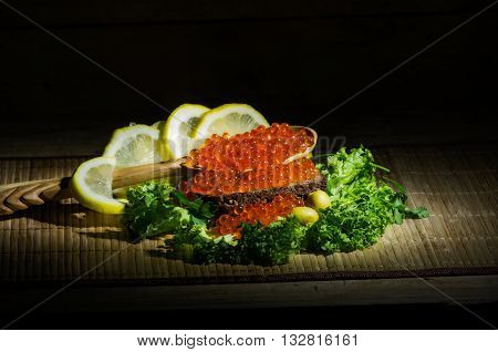 still life with red caviar black bread and fresh herbs