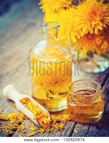 Bottle of dandelion tincture or oil flower bunch and honey jar on table. Herbal medicine. Retro styled photo.