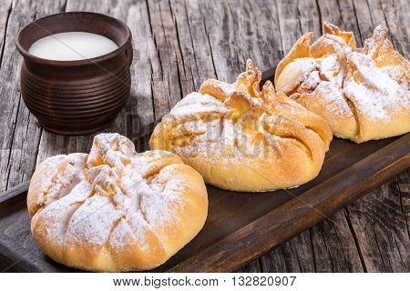 coconut puff pastries with powdered sugar dusting on a dark board on an old wooden background with milk in a clay rustic mug view from above close-up