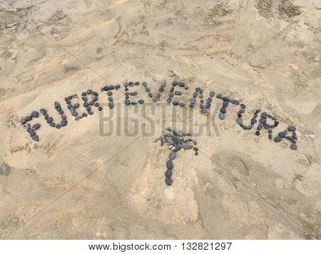 Fuerteventura, written in stones on a white sand beach on Fuerteventura island