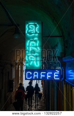 Neon light sign with bar and caffe text in Venice. Bar and caffe neon sign in tunnel with family silhouette after storm.