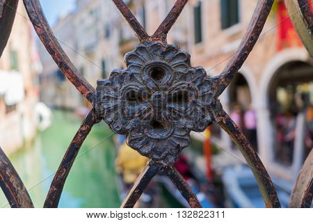 Detail on railing ornament in Venice with blurred canal and old buildings on backround.