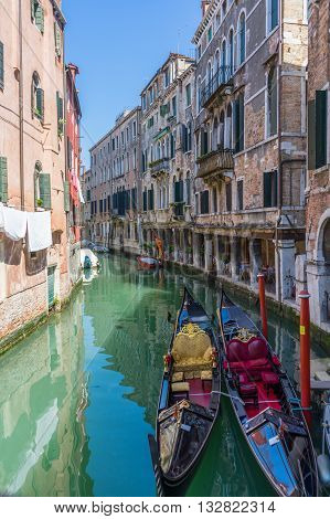 Two anchored gondolas in Venice. Venice canal with anchored gondolas colorful buildings during shiny day with clear sky.