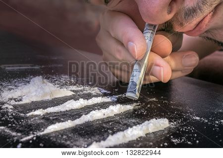 Junkie is snorting cocaine powder with rolled banknote. Narcotics concept.