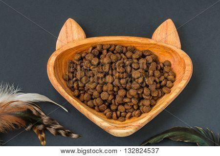 Dry cat food in a wooden bowl - shape of cat and toy teaser with feathers
