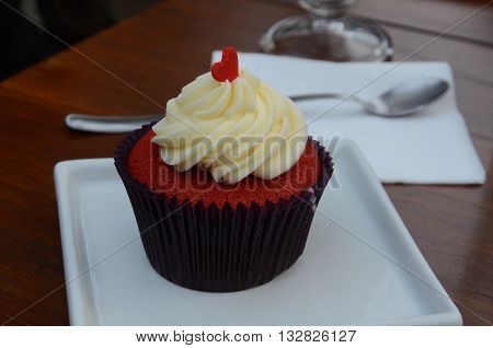 red velvet cupcake with heart ornament on