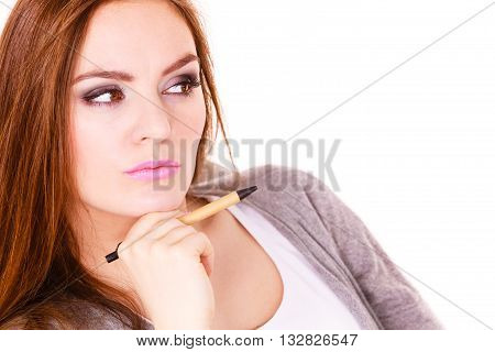 Attractive woman thinking seeks a solution doubtful young female businesswoman holding a pen making decision serious face expression