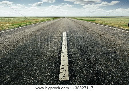 asphalt road with a marking leaving afar on a summer day. Close-up