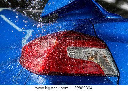 Car detailing series : Water splashing on blue car taillights