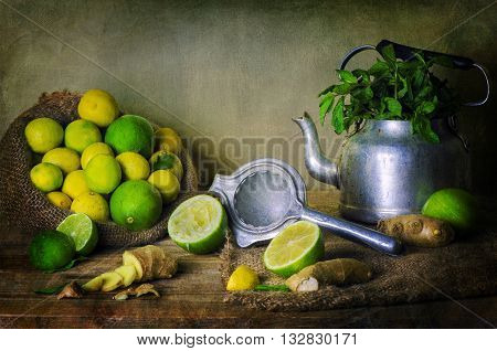 Still Life with jute bag of  fresh lemon placed with old tea kettle full of mint,old squeezer and ginger