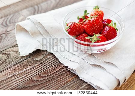 Fresh juicy strawberries in glass bowl. Rustic background with homespun napkin. Place for text.