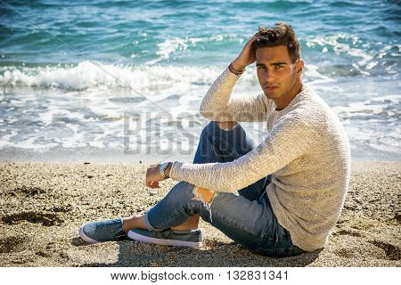 Handsome Athletic Young Man in Trendy Attire, on a Beach in a Sunny Summer Day, Looking At Camera, against Blue Sky Background.