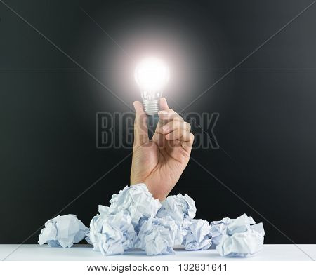 Hand hold an illuminated lightbulb with crumpled papers