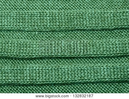 Green ribbed knit wool like texture textured fabrics knitted jersey wool as a background pattern upholstery