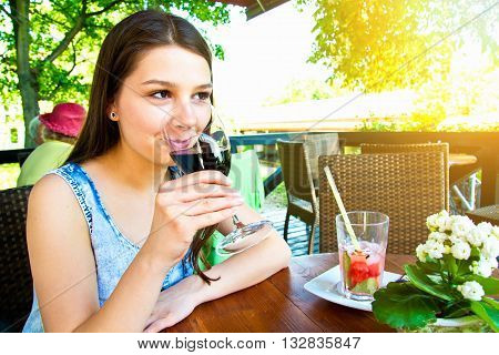 Glass of red wine drinking by young attractive women in restaurant.