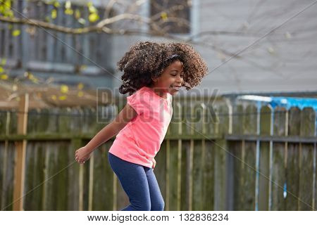 Kid toddler girl jumping on a playground in the backyard latin ethnicity