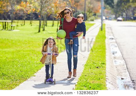 Mother daughter and son family in the park walking with ball and skate scooter