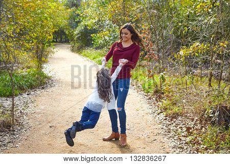 Mother and daughter being spun in circles at park having fun