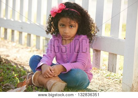 Sad toddler kid girl portrait in a park fence latin ethnicity