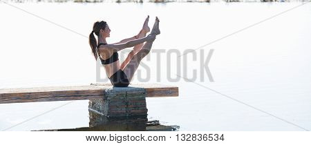 Pilates yoga workout exercise outdoor in the lake pier