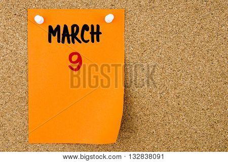 9 March Written On Orange Paper Note