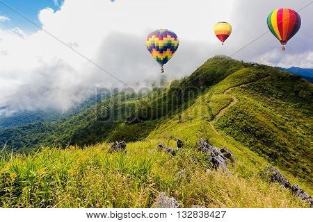 Colorful hot-air balloons flying over the mountain at Pha Tung,Chiangrai province ,North of Thailand.