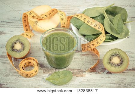 Vintage photo Fresh ingredients and green nutritious cocktail from spinach with tape measure slimming and healthy nutrition